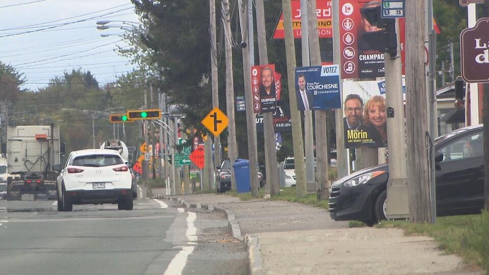 Pancartes électorales visibles sur des poteaux en bordure d'une rue passante.