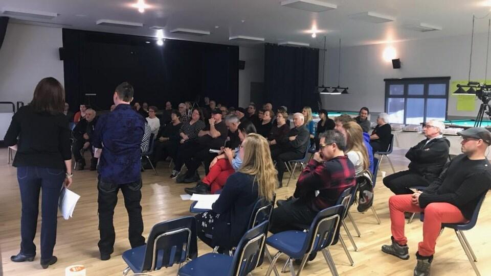 Un groupe d'une soixantaine de personnes rassemblé dans une salle.
