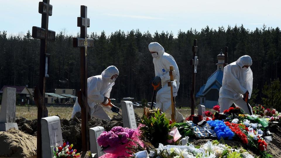 Trois travailleurs portant masque, gants et vêtement de protection creusent des tombes.