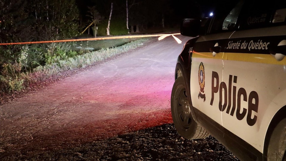Une voiture de la Sûreté du Québec sur une route, la nuit.