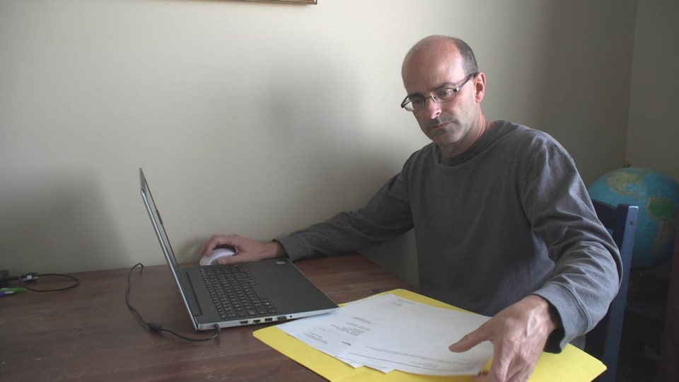 Joel Lemoine à son bureau, devant un ordinateur portable.