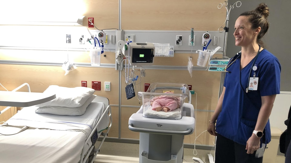 Une chambre d'hôpital avec un lit pour la mère et une couchette pour bébé.