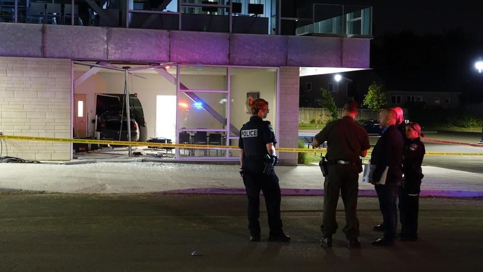 Des policiers se tiennent à l'extérieur de la bâtisse. On voit qu'une partie de la baie vitrée manque et que la voiture est encastrée dans un mur, plus loin dans le bâtiment.