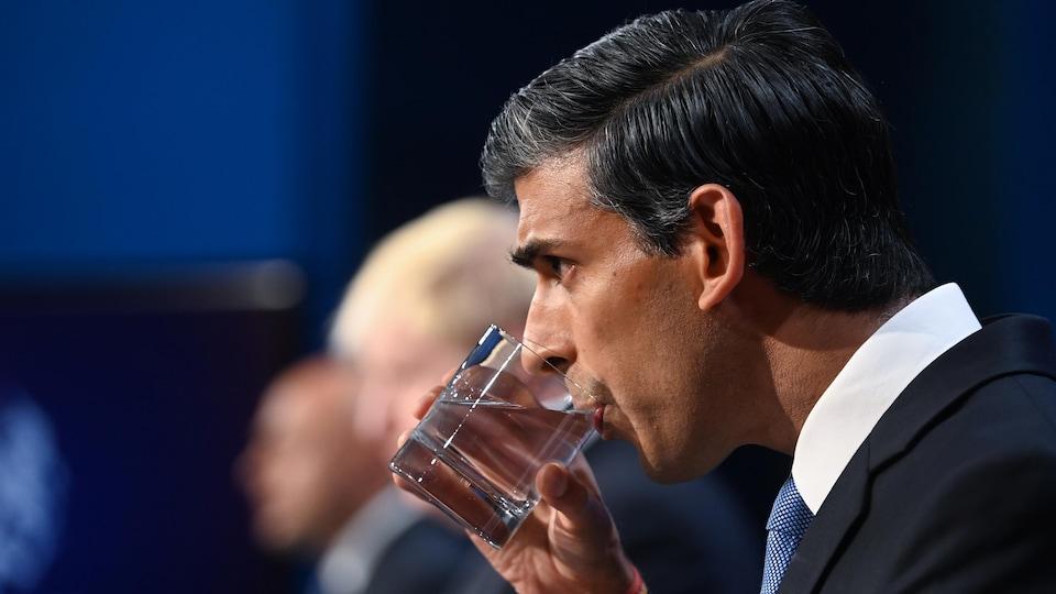 Sajid Javid boit un verre d'eau avec Boris Johnson en arrière-plan, flou.