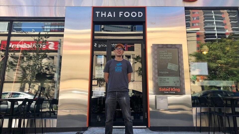 Un homme devant la façade d'un restaurant