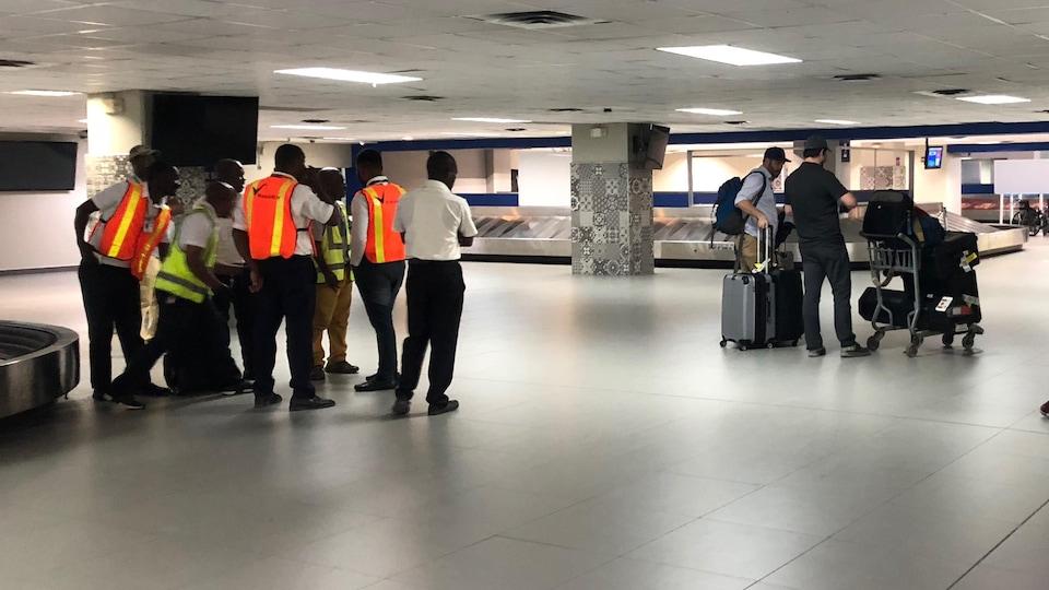 Des porteurs de bagages cherchent des bagages à porter. La salle d'arrivée de l'aéroport est désert.