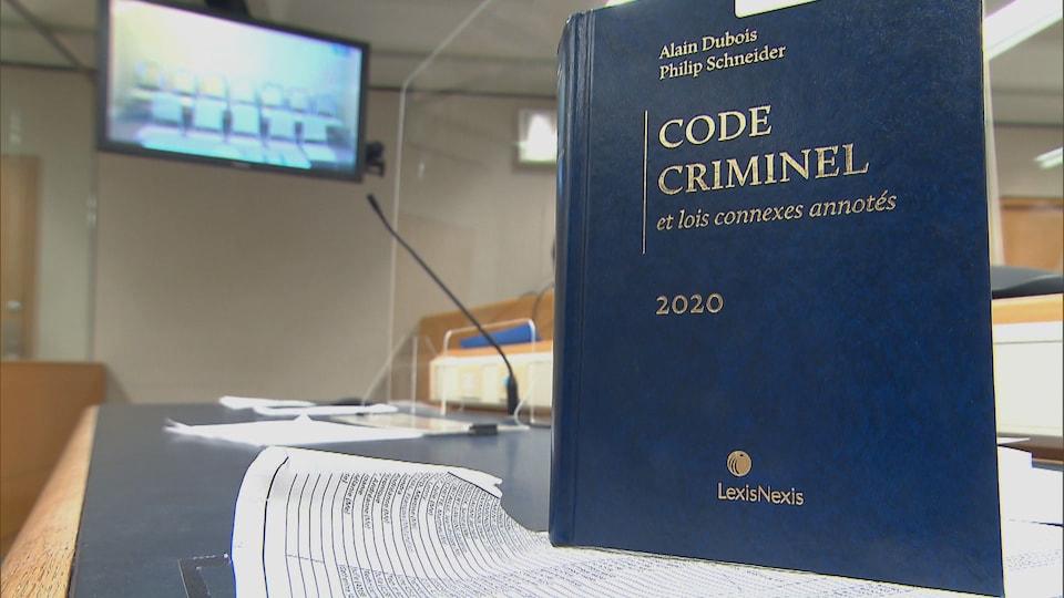 Un code criminel en avant-plan, dans une salle d'audience.