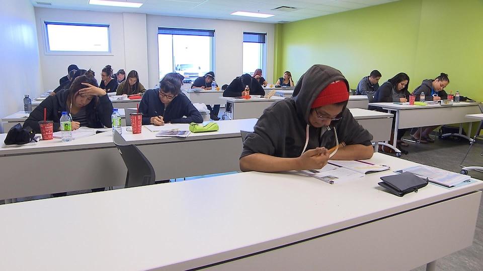 Près d'une quinzaine d'élèves travaillent dans une salle de classe spacieuse et lumineuse.