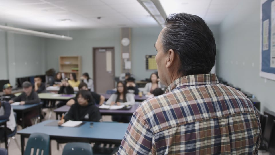 Un homme vu de dos devant une salle de classe remplie d'élèves.