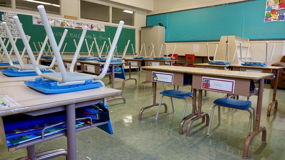 Des chaises sont retournées sur les pupitres d'une classe.