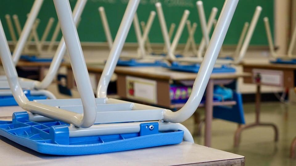 Des chaises sont retournées sur les pupitres d'une salle de classe sans élèves.