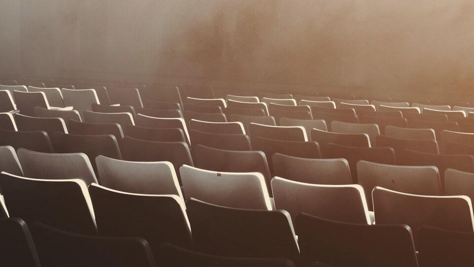 Des sièges vides dans une salle de spectacles.