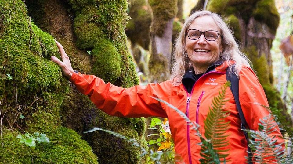 Sally Aitken, souriante, dans une forêt