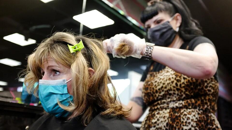 Une coiffeuse est debout derrière une cliente assise. Les deux portent un masque.
