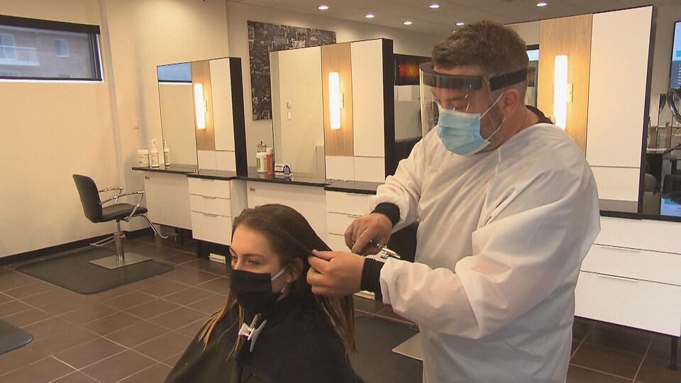Un coiffeur coupe les cheveux d'une cliente.
