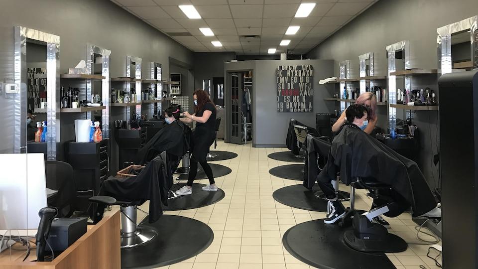 Deux coiffeuses coiffent en même temps dans un salon. Les coiffeuses et les clientes portent des masques.