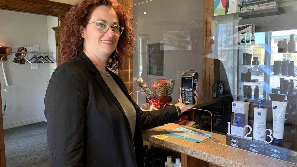 Une femme tient un terminal dans ses mains derrière une vitre.