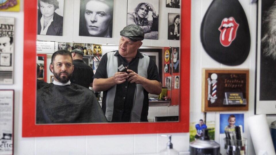 Un client se fait tailler la barbe dans un salon de barbier.