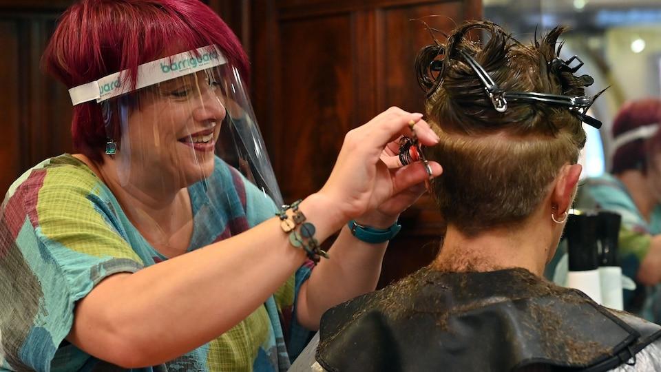 Une coiffeuse portant une visière de protection coupe les cheveux d'un client dans un salon de coiffure à Birkenhead, dans le nord-ouest de l'Angleterre, le 4 juillet 2020.
