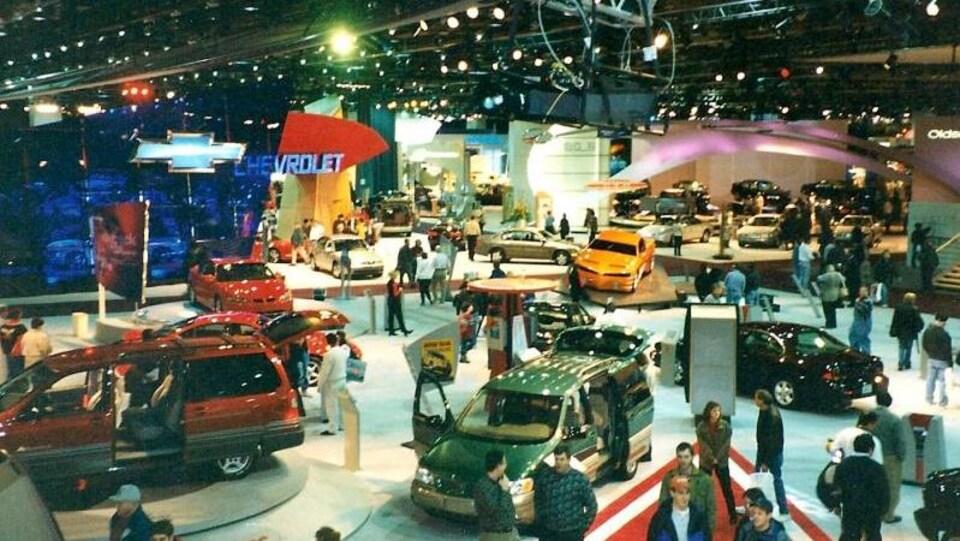 Plusieurs véhicules sont montrés au salon de l'auto, on y voit le public se promener et regarder les voitures.