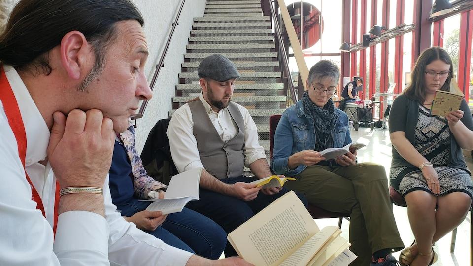 Cinq participants réunis en cercle lisent des livres.