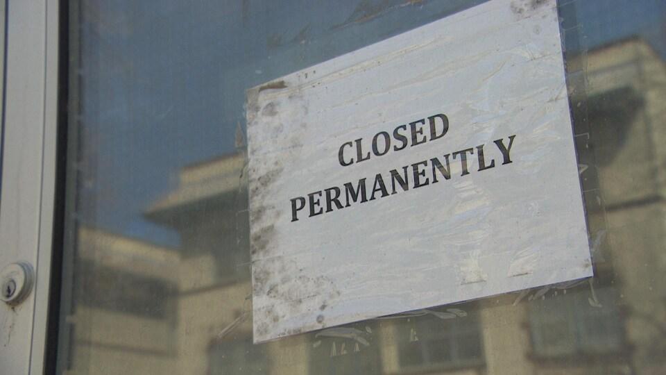 Une affiche qui indique que le commerce photographié est fermé en permanence.