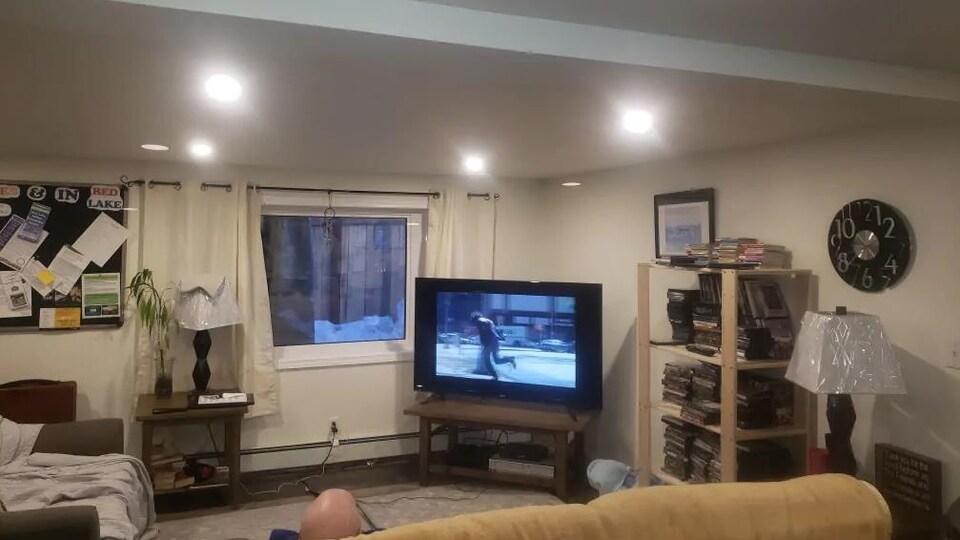 Un téléviseur, des divans et des étagères dans un salon.