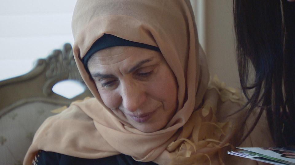 Salwa Ati regarde vers le bas. Elle a des larmes qui coulent sur ses joues.