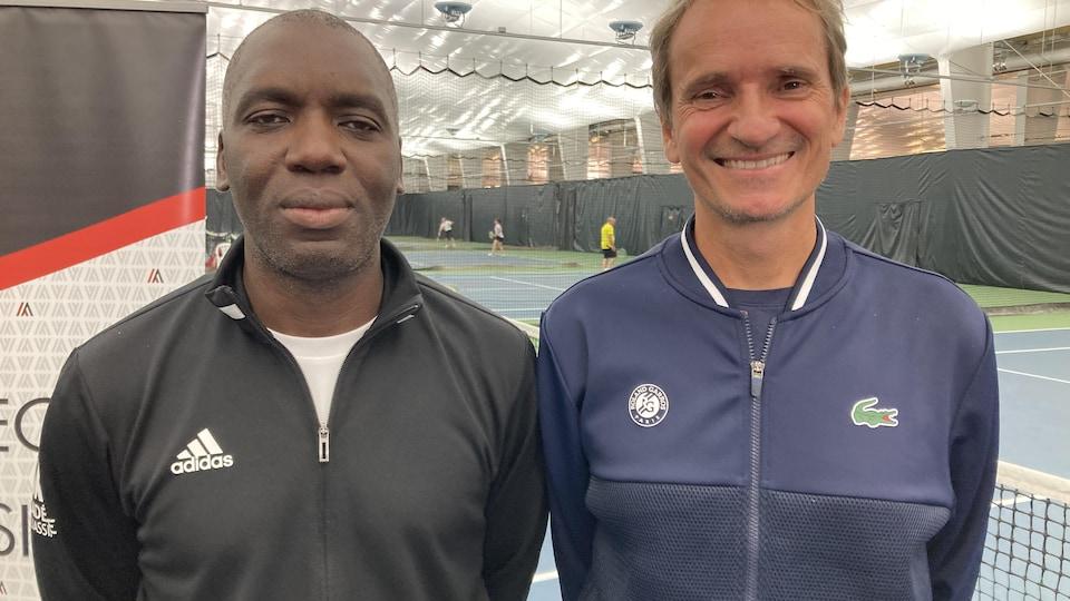 Sam et Frédéric posent pour la caméra devant un terrain de tennis.