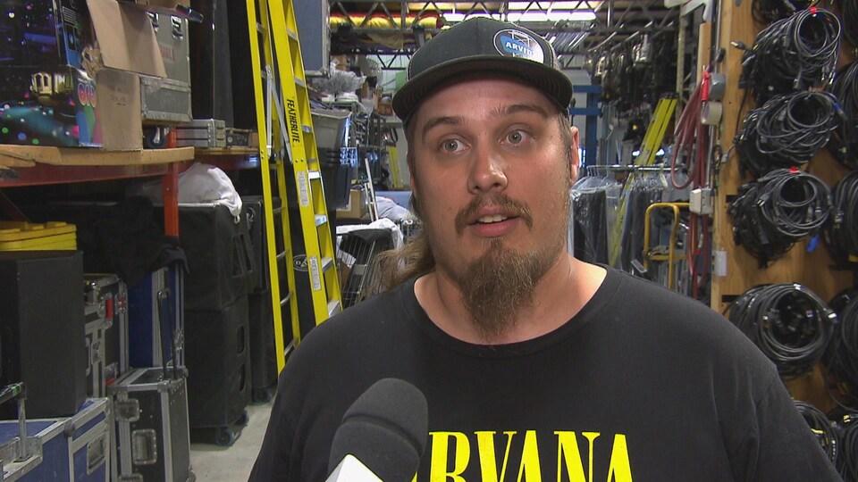 Un technicien de scène accorde une entrevue à une journaliste dans un entrepôt débordant de fils et de boîtes.