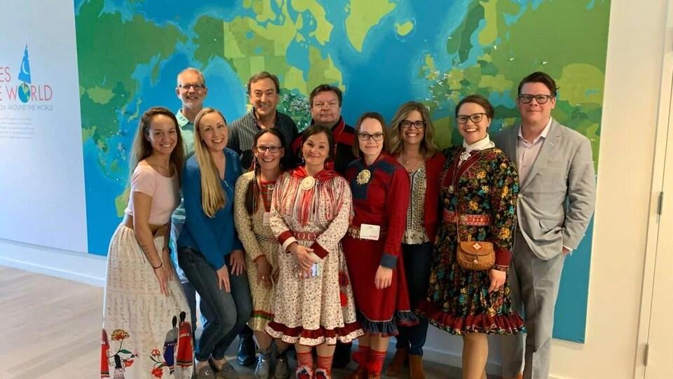 Un groupe de personnes pose devant une carte du monde.