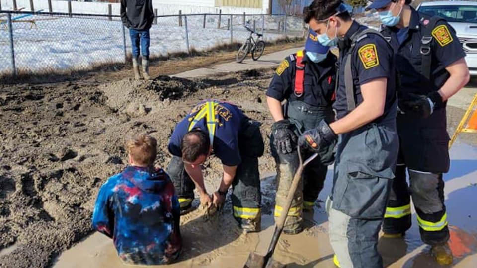 Un garçon pris dans un trou de vase jusqu'à la taille, autour de lui quatre pompiers avec une pelle. Un garçon regarde la scène du trottoir.