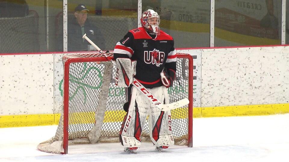 Un gardien de but de hockey en uniforme devant son filet lors d'un match.