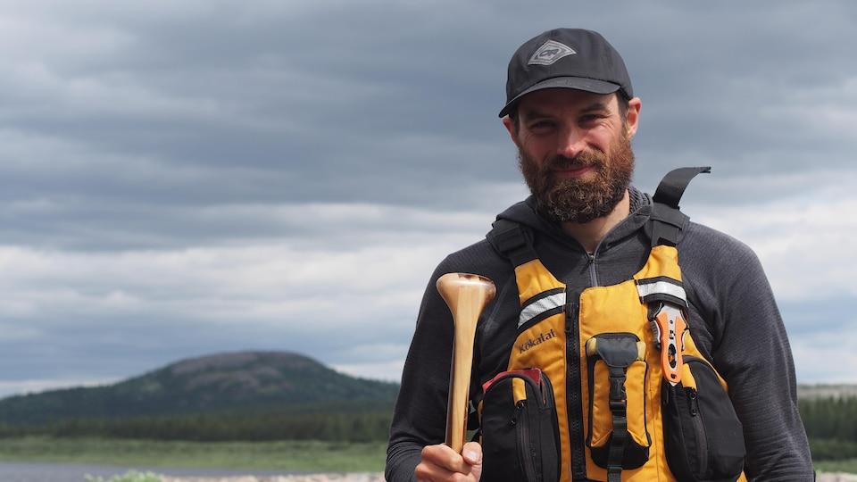 Samuel Lalande-Markon tient une rame près d'un plan d'eau.