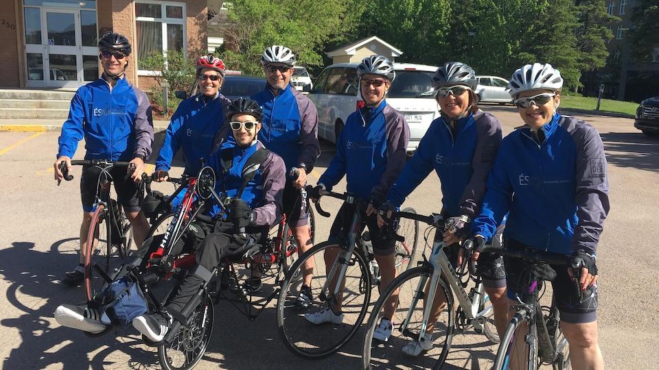Un groupe de cyclistes sont sur leur vélo et sourient à la caméra.