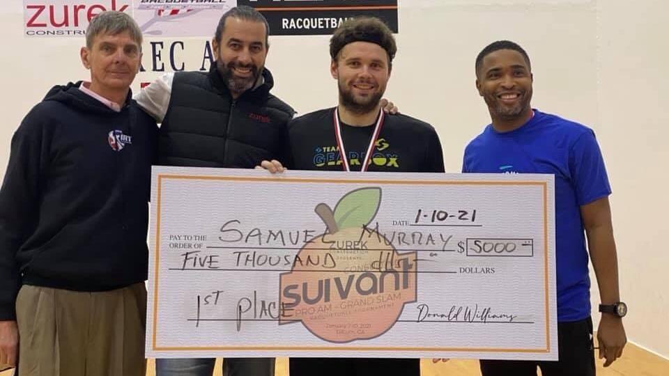 Quatre hommes dont Samuel Murray derrière un chèque géant de 5000 $.