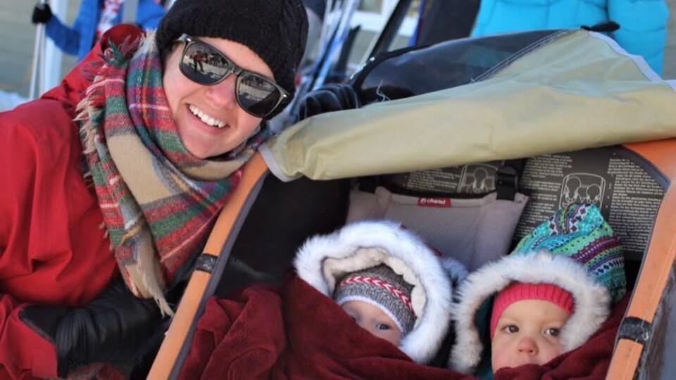 Samuelle Ramsay-Houle est à côté de la poussette dans laquelle sont assis ses deux jeunes enfants.