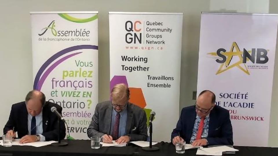 Trois hommes signent un protocole.
