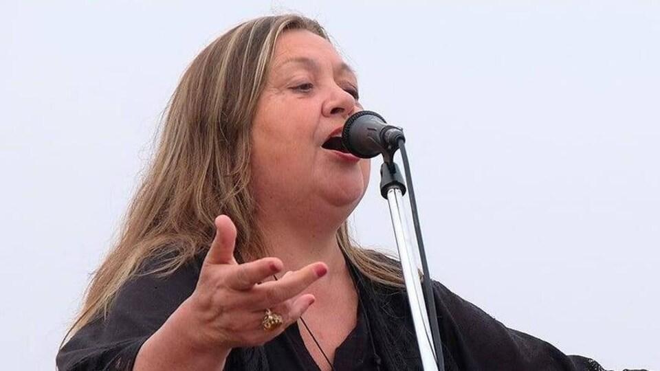 Sandra Le Couteur, chantant derrière un micro