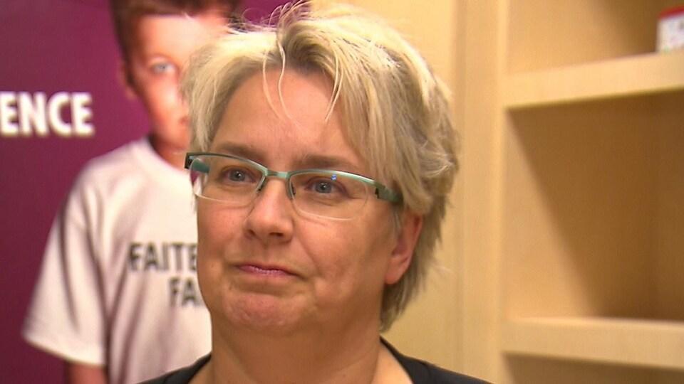 Sandra Morin, porte des lunettes et les cheveux courts blonds; elle semble écouter une personne qu'on ne voit pas.