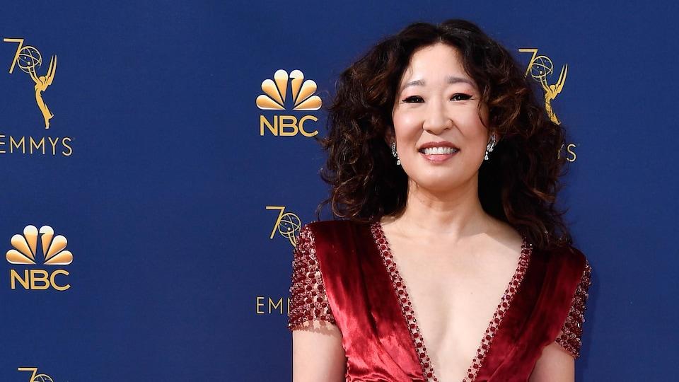 Une femme vêtue d'une robe rouge sourit devant un fond bleu au logo de NBC.