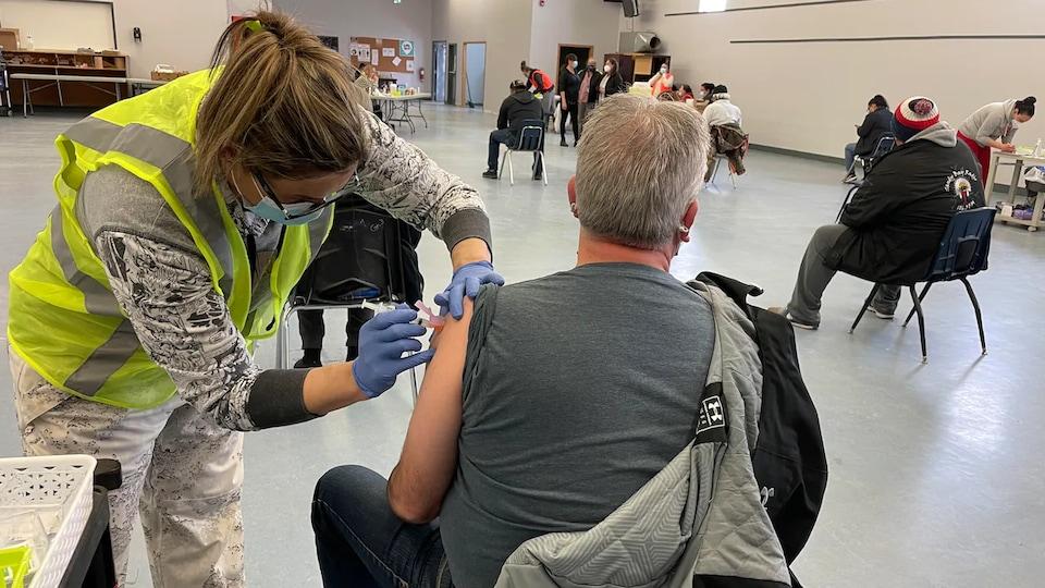 Des gens de dos qui se font vacciner.