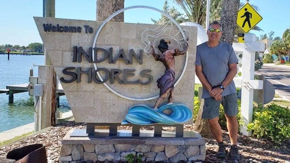 Sandy MacNeill pose à côté d'un monument qui annonce Indian Shores, en Floride.