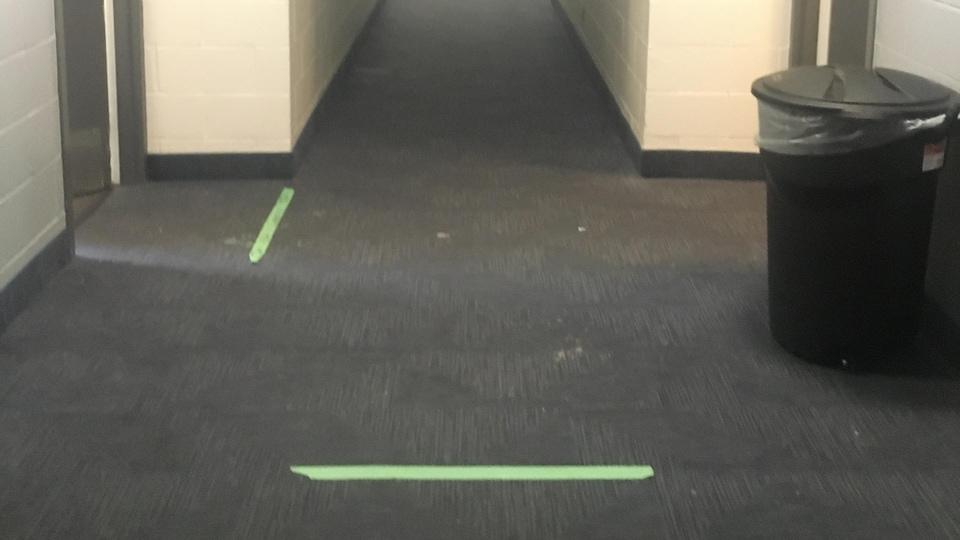 Un corridor dans un motel avec bandes vertes au sol