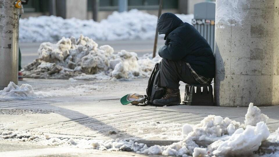 Un homme mendie dans une ville enneigée