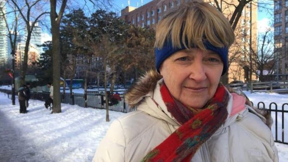 On aperçoit la militante Cathy Crowe dehors sur un trottoir par temps froid à Toronto.