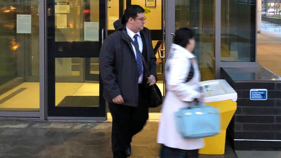 On voit l'agent James McKrell de la police de Toronto sortir de la cour du coroner avec sa femme.