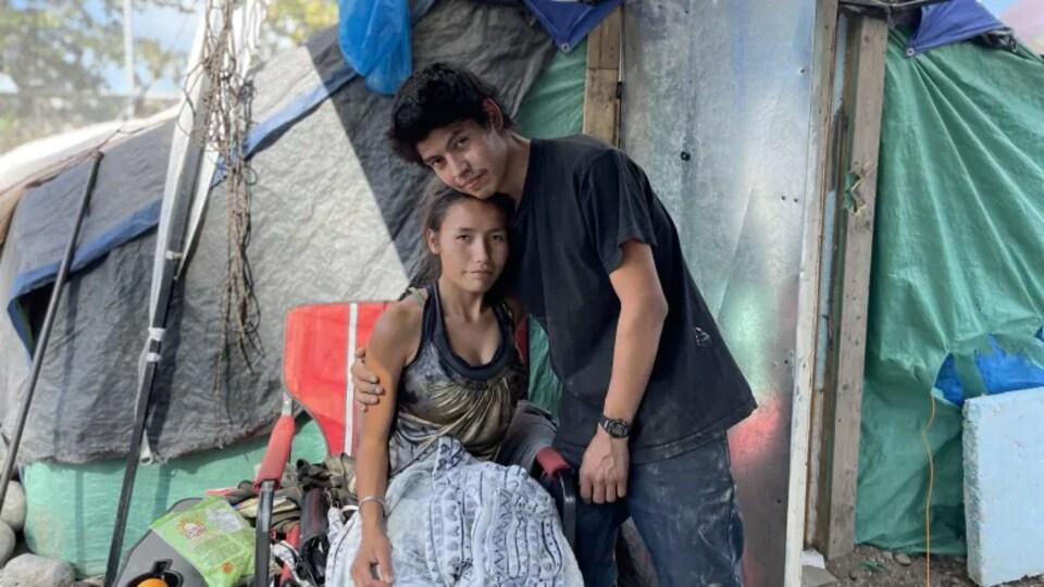 Un homme et une femme devant un tente en ville.