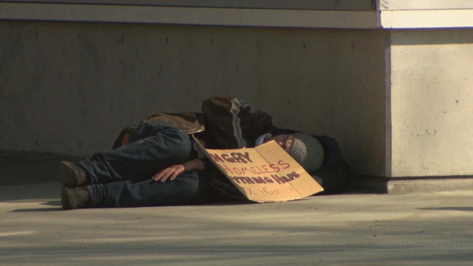 Un sans-abri est allongé sur le trottoir avec une pancarte en carton dans le Downtown Eastside, à Vancouver.