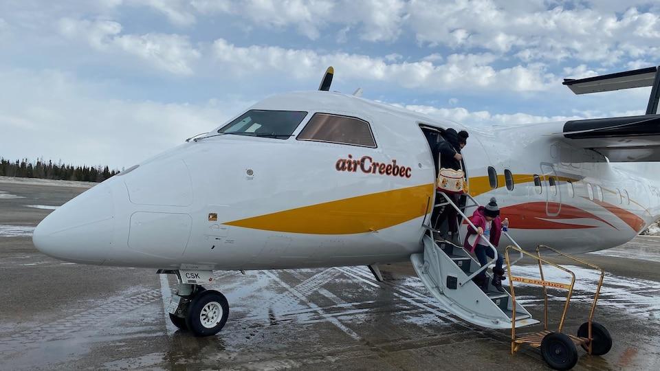 Un avion avec une femme et un enfant qui descendent
